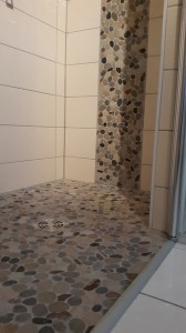 Dusche mit Bodenablauf und Mosaik Flusskiesel